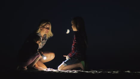 Mom-With-Two-Daughters-Playing-In-The-Sand-On-The-Beach-In-The-Late-Evening-They-Light-The-Ground-Wi