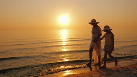 Summer-Vacation-With-A-Child---A-Woman-With-Her-Daughter-Strolling-Along-The-Seashore-At-Sunset-Stea