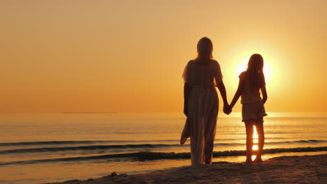 A-Woman-Holds-A-Child-s-Hand-Stand-Together-On-The-Seashore-Look-At-A-Beautiful-Sunset-Mother-With-D