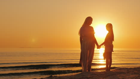 Mom-And-Daughter-Are-Looking-Forward-To-A-Beautiful-Sunset-Over-The-Sea-Silhouettes-Of-A-Woman-With-