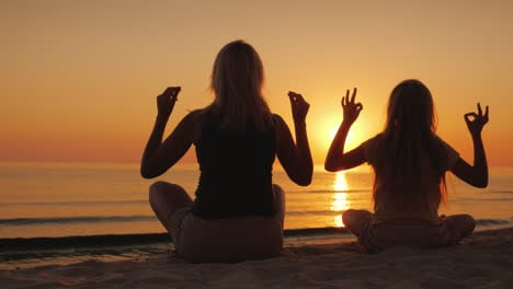 Mom-And-Daughter-Are-Meditating-By-The-Sea-At-Sunset-Health-And-Happy-Time-Together