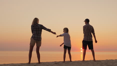 A-Young-Mother-With-Two-Niños-Is-Teaching-A-Fashionable-Dance-Movement-On-The-Beach-At-Sunset-Com