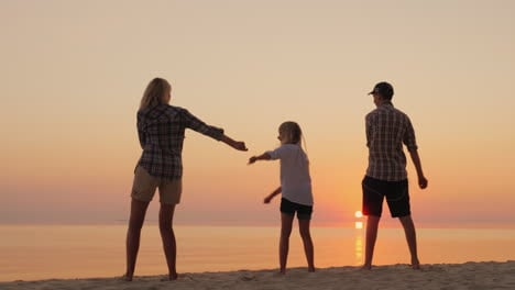 A-Young-Mother-With-Two-Children-Is-Teaching-A-Fashionable-Dance-Movement-On-The-Beach-At-Sunset-Com
