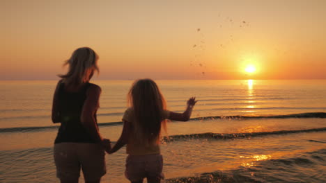 Mom-And-Daughter-Are-Walking-On-The-Water-Against-The-Backdrop-Of-The-Setting-Sun