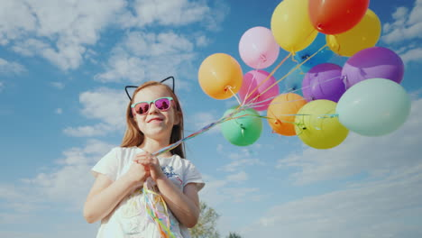 A-Cheerful-Girl-With-Balloons-Is-Standing-On-A-Green-Meadow-Enjoy-The-Warmth-And-Fly-Of-The-Concept