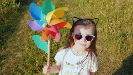 Portrait-Of-A-Stylish-Little-Girl-With-A-Toy-Windmill-In-Her-Handst