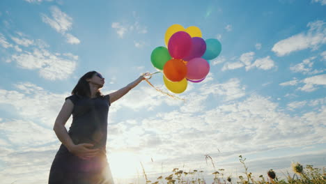 Happy-Pregnant-Woman-Playing-With-Balloons-Against-The-Blue-Sky