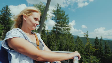 An-Active-Woman-Enjoys-A-Ride-On-A-Cable-Car-Over-A-Forest-Surrounded-By-Mountains-4K-Video