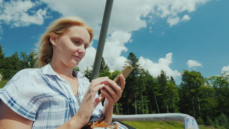 A-Woman-Uses-A-Smartphone-Rides-In-The-Open-Cabin-Of-The-Cable-Car-On-Vacation-In-Connection-With-Th