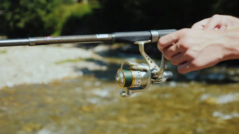 Fisherman-s-Hands-With-Spinning-Fishing-Near-A-Small-Mountain-River
