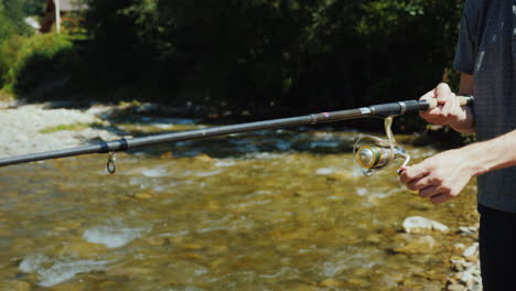 A-Young-Man-Is-Fishing-Around-A-Small-River-A-Side-View-Only-The-Hands-Are-Visible-In-The-Frame