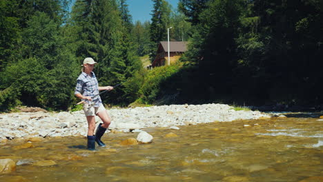 A-Young-Woman-In-Rubber-Boots-With-A-Fishing-Rod-Turns-Into-A-Ford-Of-A-Mountain-River-Activities-In