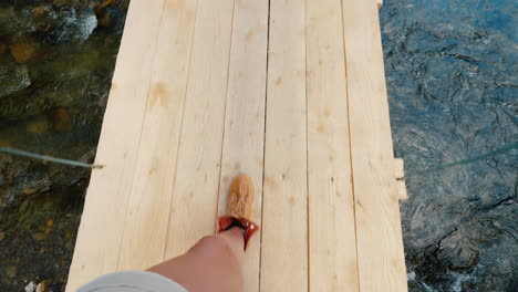 A-Man-In-Trekking-Boots-Walks-Along-The-Edge-Of-A-Wooden-Bridge-Over-The-Precipice-Pov-Video