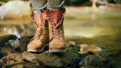 A-Tourist-In-Trekking-Boots-Stands-Near-A-Mountain-Stream-Hiking-And-Active-Rest