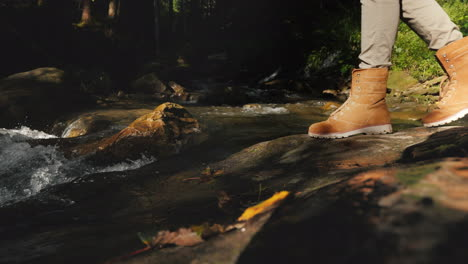 A-Traveler-In-Hiking-Boots-Passes-Through-Slippery-Stones-Only-The-Legs-Are-Visible
