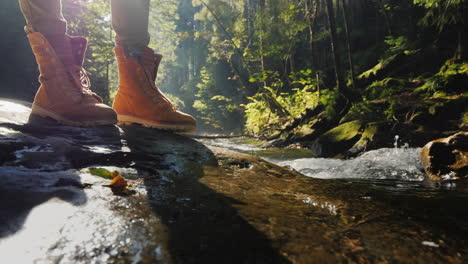 The-Feet-Of-The-Traveler-Stand-On-A-Wet-Log-Near-A-Mountain-Stream-Tourism-And-Hiking-Conceptt