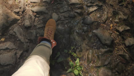 A-Man-In-Trekking-Boots-Walks-Along-A-Slippery-Stony-Path-In-The-Forest-First-Person-Video-Hiking-An