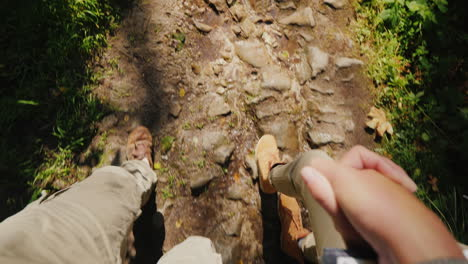 A-Couple-Of-Tourists-Hold-Hands-And-Walk-On-A-Slippery-Stony-Path-In-The-Forest-Only-The-Legs-Are-Vi