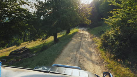 Riding-An-Off-Road-Vehicle-On-An-Extremely-Bad-Road-Through-The-Forest-The-Setting-Sun-Shines-Throug