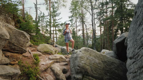 A-Woman-With-A-Backpack-On-Her-Back-Is-Standing-On-Huge-Stones-In-The-Forest-Walking-And-Active-Life