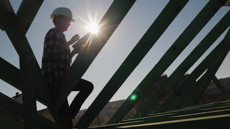 Silhouette-Of-An-Engineer-Works-Among-The-Rafters-Of-The-Roof-Uses-A-Tablet-Technical-Control-In-Con