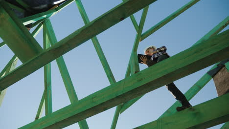 Female-Builder-Working-With-A-Tablet-Among-The-Rafters-Of-An-Unfinished-Roof