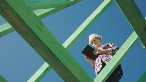 A-Female-Architect-Is-Working-With-A-Tablet-Among-The-Rafters-Of-The-Roof-Architectural-Supervision-