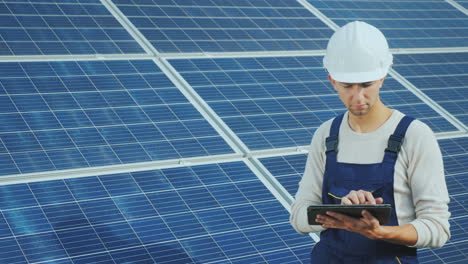 Young-Engineer-In-White-Helmet-Works-With-A-Tablet-On-The-Background-Of-Solar-Panels
