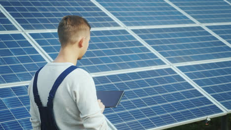 The-Engineer-Uses-The-Tablet-On-The-Background-Of-Solar-Panels-Alternative-Energy-And-Solar-Energy