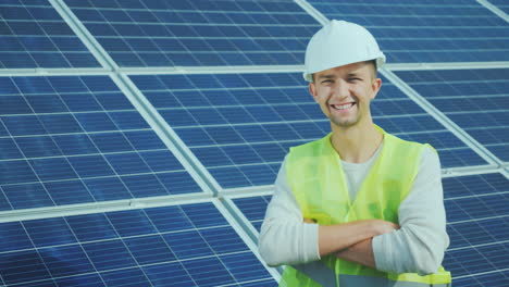 Portrait-Of-A-Worker-In-Overalls-And-A-Helmet-On-The-Background-Of-Solar-Panels-Smiles-Looks-Into-Th