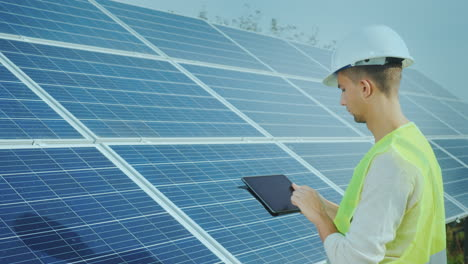A-Good-Looking-Worker-Uses-A-Tablet-Near-Ground-Based-Solar-Panels