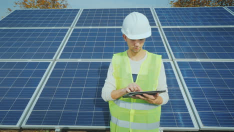 Young-Engineer-Working-With-A-Tablet-On-The-Background-Of-A-Ground-Based-Solar-Power-Station