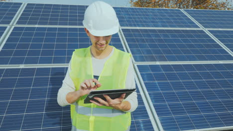 A-Worker-In-A-Helmet-Works-With-A-Tablet-Near-A-Ground-Based-Solar-Power-Station