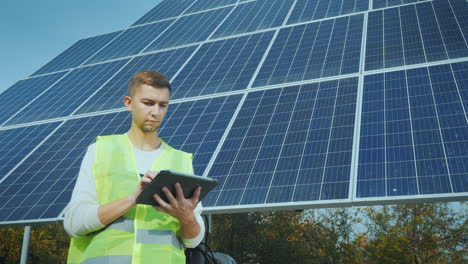 A-Young-Engineer-In-Workwear-Works-With-A-Tablet-Near-A-Large-Solar-Panel