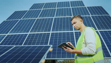 A-Worker-Uses-A-Tablet-In-A-Large-Ground-Based-Solar-Panel-Alternative-Energy