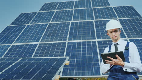 A-Young-Businessman-In-A-White-Helmet-Uses-A-Tablet-On-The-Background-Of-Solar-Panels-Alternative-En