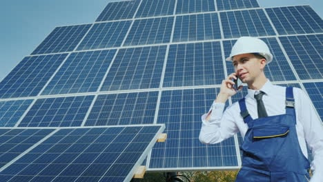 Young-Engineer-Talking-On-The-Phone-On-The-Background-Of-A-Large-Solar-Panel