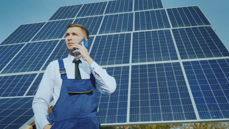 Young-Engineer-Speaks-On-The-Phone-On-The-Background-Of-Large-Solar-Panels