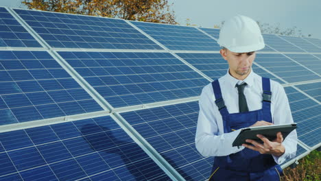 Engineer-In-Overalls-Over-A-Business-Suit-Stands-Near-The-Solar-Panel-Uses-A-Tablet