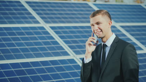 Successful-Businessman-Talking-On-The-Phone-On-The-Background-Of-A-Solar-Power-Station