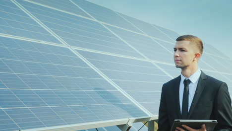 Businessman-With-A-Tablet-In-His-Hands-Goes-Along-A-Row-Of-Solar-Panels-Development-Of-Alternative-E