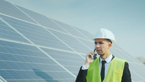 An-Engineer-Walks-Along-The-Solar-Panels-Talking-On-The-Phone