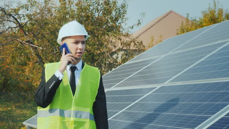 A-Worker-In-A-Helmet-Walks-Along-A-Row-Of-Solar-Panels-Speaks-On-The-Phone