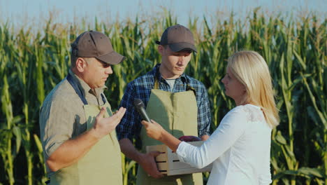 A-Reporter-With-A-Microphone-Records-Interviews-With-Two-Farmers-Stand-In-The-Field-Against-The-Back