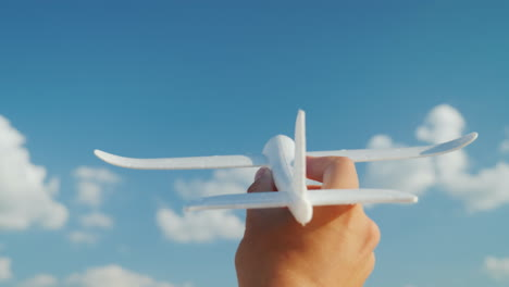 A-Male-Hand-Holds-A-Toy-Airplane-Directed-To-The-Sky-Idea-And-Dream-In-Business-Concept-4K-Video