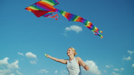 Happy-Woman-As-A-Child-Plays-With-An-Air-Kite-On-A-Background-Of-Pure-Blue-Sky-4K-Video