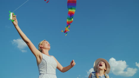 A-Carefree-Woman-Plays-With-Her-Daughter-A-Girl-Tries-To-Catch-An-Air-Kite-Against-The-Background-Of