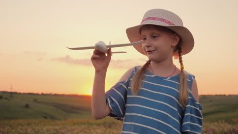 A-Girl-With-Pigtails-And-A-Hat-Playing-With-A-Wooden-Airplane-At-Sunset-The-Dream-Of-Long-Distance-T