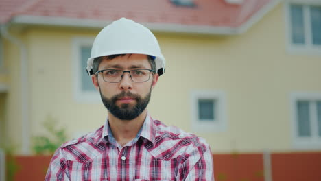 Portrait-Of-An-Attractive-Engineer-In-A-White-Helmet-It-Looks-At-The-Camera-Against-The-Backdrop-Of-