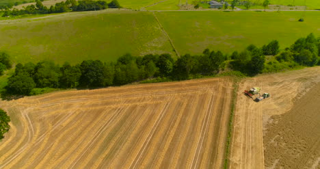 Combine-Harvester-And-Tractor-Working-In-Agricultural-Field-